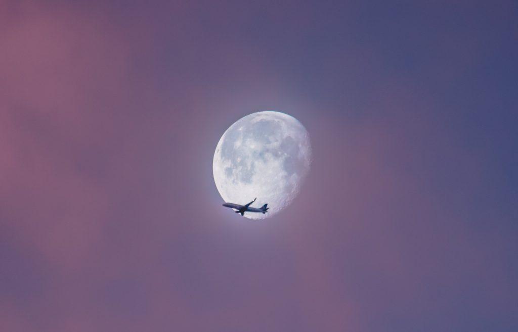 lecący samolot na tle pełni księżyca