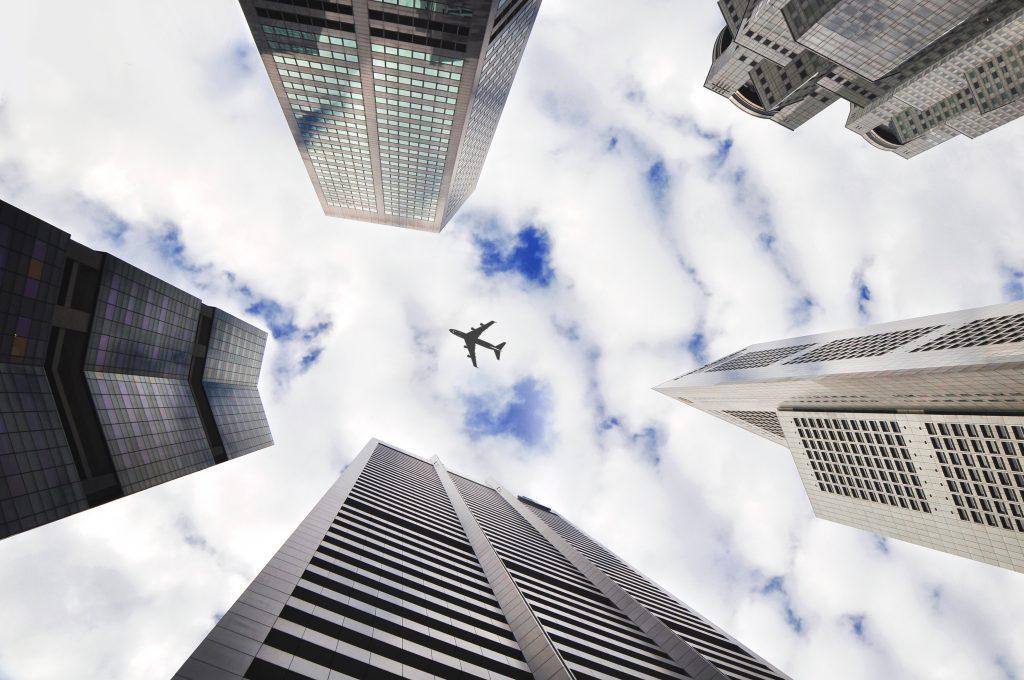 samolot lecący pomiędzy drapaczami chmur