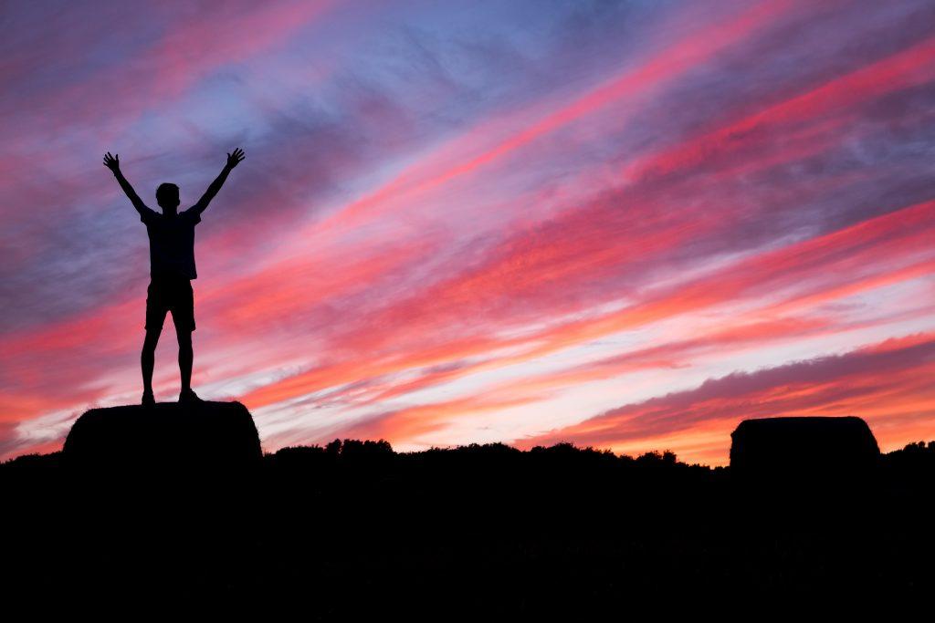 mężczyzna sięgający nieba w zachódzie słońca
