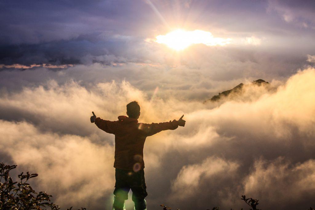 mężczyzna stojący na szczycie góry